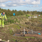 <span class=heading><b>Unearthing the potential beneath</b> by Keith Torrance</span><br />In partnership with Scottish Canals, Strathclyde researchers are aiming to transform noxious, wet canal sediments into useful construction materials, investigating new processes to naturally improve them. One method is to encourage grass and other plants to remove water and break-down any remaining contaminants, improving the texture of the soil. In this photo, we are preparing the surface of a sediment lagoon for over-seeding with a resistant grass variety.<br /><span class=small>Image: © 2021 Keith Torrance</span>. <span class=small>Collaborators: Richard Lord (photo subject)</span>