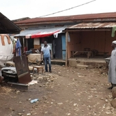 """<div><div style=""""float:left;padding-left:5px;width:70%""""><span class=heading><b>From contested to common grounds</b> by Aisha Abubakar</span><br />Adam looks on proudly at his home/blacksmith-workshop at a city-centre slum in Abuja. He is among a continuously growing population residing in different slum types within cities of the global south. Interestingly, both city system and slum have the same comparative focus: prosperity. Identifying and analysing relative features, in slums, that either impede or enhance prosperity is imperative, as motive and design guide, for better targeted integrative slum management programs.<br /><span class=small>Image: &copy; 2015 Aisha Abubakar</span>. &nbsp;<span class=small>Collaborators: Dr Ombretta Romice; Dr Ashraf salama</span></div><div style=""""float:right;padding-right:5px;""""><iframe width=""""280"""" height=""""170"""" src=""""https://www.youtube.com/embed/Tj3XcTrEd_Y"""" frameborder=""""0"""" allowfullscreen></iframe></div></div>"""