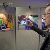 <span class=heading><b>Images of Research</b> by Guy Hinks</span><br /><p class=int>Judge Chris Thomson watches the ditigtal stories developed by entrants through augmented reality technology, Aurasma.</p><span class=small>Image: &copy; 2018 Guy Hinks 2015</span>