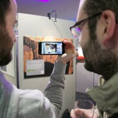 <span class=heading><b>Images of Research</b> by Guy Hinks</span><br /><p class=int>Delegates using the augmented reality technology app, Aurasma, to watch the researcher&rsquo;s stories come to life on their phones!</p><span class=small>Image: &copy; 2018 Guy Hinks 2015</span>