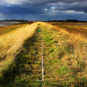 <span class=heading><b>Clouds of Change</b> by Marcin Zielinkski (Department of Civil & Environmental Engineering)</span><br /><p class=int>The picture presents the flood embankment located along river Humber in North-East of England, East Airshire. It was taken during geophysical survey which was looking at the desiccation crack detection in flood protection structures. The picture shows the perfect match between the dramatic dark clouds which are the source of rain causing flooding, and the shiny embankment which protects against flooding. Will embankments protect us ?</p><span class=small>Image: © 2012 Marcin Zielinkski</span>